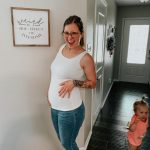 Woman, 16 weeks pregnant posing with baby bump.